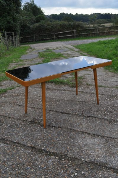 Black vitrolite-topped coffee table